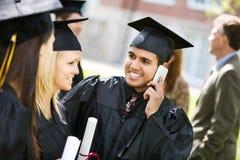 Graduación: El graduado llama a la familia después de ceremonia Imagen de archivo libre de regalías