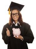 Graduación que sostiene la hucha rosada Imagenes de archivo