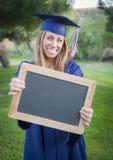 Graduado adolescente con el casquillo que lleva y el vestido de la pizarra en blanco Fotos de archivo libres de regalías