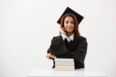 Graduado africano de la hembra en sentarse sonriente del casquillo y de la capa con los libros sobre el fondo blanco Fotografía de archivo libre de regalías