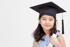 Graduado asiático del niño de la escuela en casquillo de la graduación Foto de archivo libre de regalías