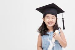 Graduado asiático del niño de la escuela en casquillo de la graduación Imágenes de archivo libres de regalías