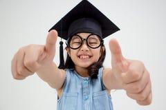 Graduado asiático feliz da criança da escola no tampão da graduação Fotografia de Stock
