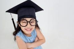 Graduado asiático feliz da criança da escola no tampão da graduação imagem de stock royalty free