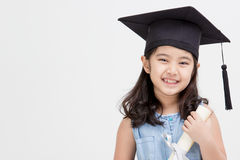 Graduado asiático feliz del niño de la escuela en casquillo de la graduación Foto de archivo libre de regalías