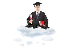 Graduado de faculdade masculino que mantém o diploma e os livros assentados na nuvem imagens de stock royalty free