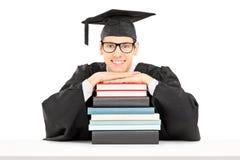 Graduado de faculdade que levanta atrás de uma pilha de livros imagem de stock