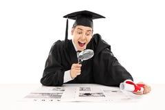 Graduado de faculdade que procura pelo trabalho no jornal fotos de stock