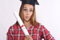 Graduado de la chica joven con el casquillo y el diploma Fotografía de archivo libre de regalías