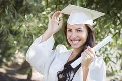 Graduado de la hembra de la muchacha de la raza mixta en casquillo y vestido con el diploma Foto de archivo libre de regalías
