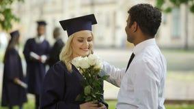 Graduado de la hembra en regalía académica con las flores que habla con el novio, educación almacen de metraje de vídeo