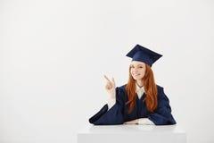 Graduado de la hembra que sonríe señalando el finger en el lado que se sienta sobre el fondo blanco Copie el espacio Imagenes de archivo