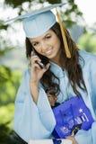 Graduado de la hembra que usa el teléfono celular Foto de archivo libre de regalías