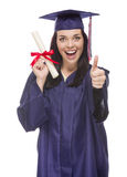 Graduado de la raza mixta en el casquillo y el vestido que sostienen su diploma Fotos de archivo