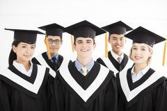 Graduado de universidad en la graduación con los compañeros de clase Imágenes de archivo libres de regalías