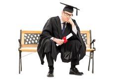 Graduado de universidad enojado que sostiene un diploma Foto de archivo