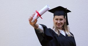 Graduado de universidad feliz que muestra su nuevo diploma de la graduación almacen de metraje de vídeo