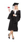 Graduado de universidad femenino que sostiene un diploma Foto de archivo