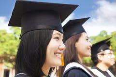 Graduado de universidad femenino sonriente que se coloca con el compañero de clase Foto de archivo