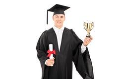 Graduado de universidad masculino que sostiene un trofeo de oro Imagen de archivo libre de regalías