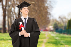 Graduado de universidad orgulloso que sostiene el diploma en parque fotos de archivo libres de regalías