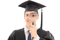 Graduado de universidad que mira a través de la lupa Foto de archivo libre de regalías