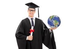 Graduado de universidad que sostiene un diploma y el mundo Foto de archivo libre de regalías