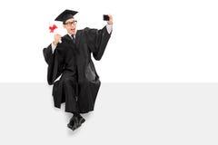 Graduado de universidad que toma el selfie asentado en un panel Imagen de archivo