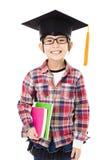 graduado del niño de la escuela en casquillo de la graduación Imágenes de archivo libres de regalías