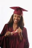 Graduado fêmea da faculdade no tampão e no vestido Foto de Stock Royalty Free