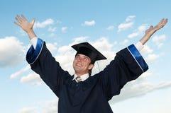 Graduado feliz con los brazos levantados Fotografía de archivo libre de regalías