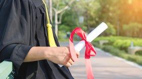 Graduado feliz que mostra disponivel habilitado Fotografia de Stock Royalty Free
