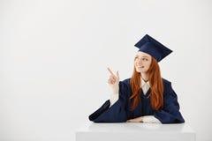 Graduado femenino joven de la universidad en el casquillo académico que se sienta en señalar sonriente de la tabla a la izquierda Foto de archivo libre de regalías