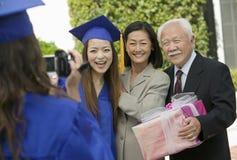 Graduado grabando otro graduado con la madre y el abuelo afuera Imagenes de archivo
