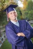 Graduado hermoso del varón en casquillo y vestido Foto de archivo