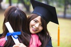 Graduado novo que abraça seu amigo na cerimônia de graduação fotografia de stock royalty free
