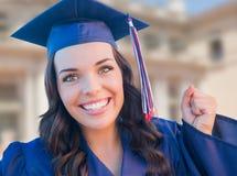 Graduado sonriente de la hembra de la raza mixta en la celebración del casquillo y del vestido Foto de archivo