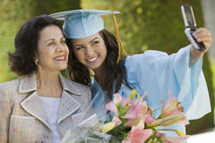Graduado y abuela que toman la imagen con el teléfono móvil Imágenes de archivo libres de regalías