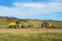 Graduador e escavadora na construção da estrada Imagem de Stock