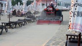 Graduador que tamiza la arena en la playa pública almacen de video