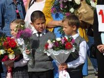 Graduadores pela primeira vez na escola a régua solene no primeiro setembro Imagem de Stock