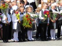 Graduadores pela primeira vez na escola a régua solene no primeiro setembro Imagens de Stock