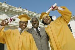 Graduados con el padre Outside University Fotos de archivo