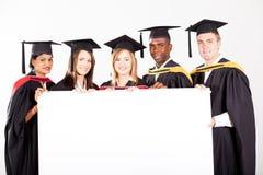 Graduados con la tarjeta blanca Foto de archivo libre de regalías