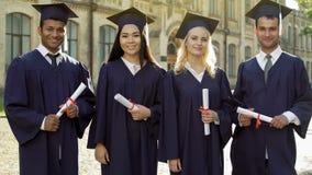 Graduados de faculdade na insígnia real acadêmico que guarda os diplomas, comemorando a graduação fotos de stock