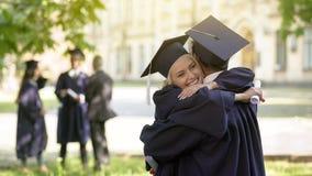Graduados de faculdade que têm a conversação, abraçando-se, amizade da universidade fotografia de stock royalty free