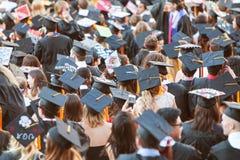 Graduados de faculdade que vestem o recolhimento dos barretes para atividades da graduação fotos de stock royalty free