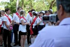 Graduados de la escuela delante de las cámaras Foto de archivo