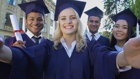 Graduados de universidad que toman el selfie el día de graduación que dice el queso, amistad almacen de video