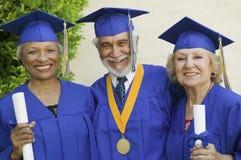 Graduados do sénior que sorriem fora Fotografia de Stock Royalty Free